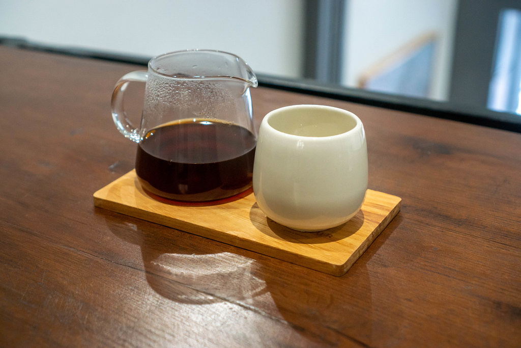 Small Glass Jug with Hot Dripping Coffee on a Wooden Serving Board with a White Ceramic Cup
