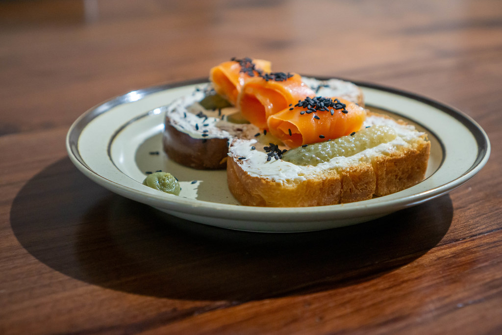 Close Up Photo of two Slices of White Bread with Cream Cheese, Pickled Cucumbers, Smoked Salmon, Sesame and Horseradish on a Plate