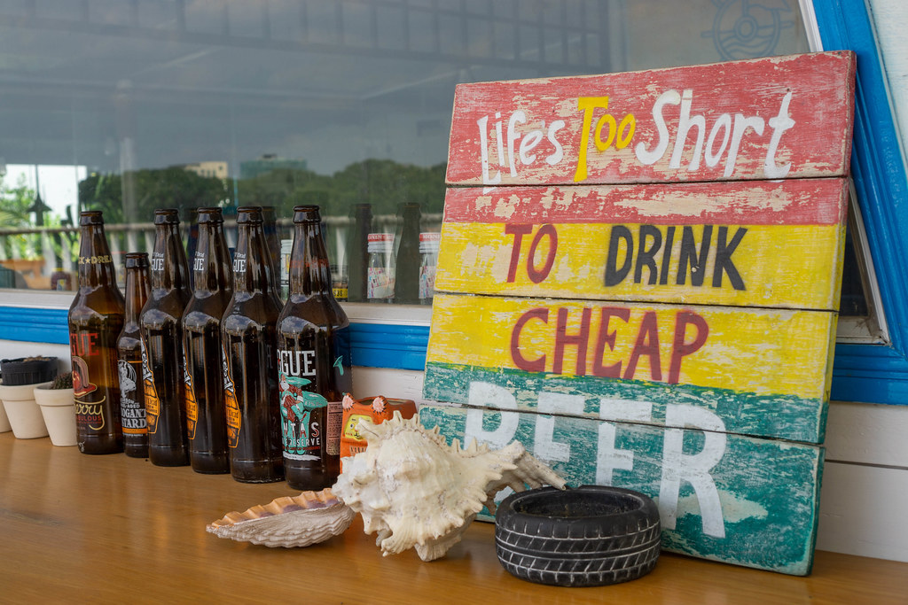 Empty Beer Bottles, Seashells and Wooden Board with Saying as Decoration at an Outdoor Bar Space in Saigon, Vietnam