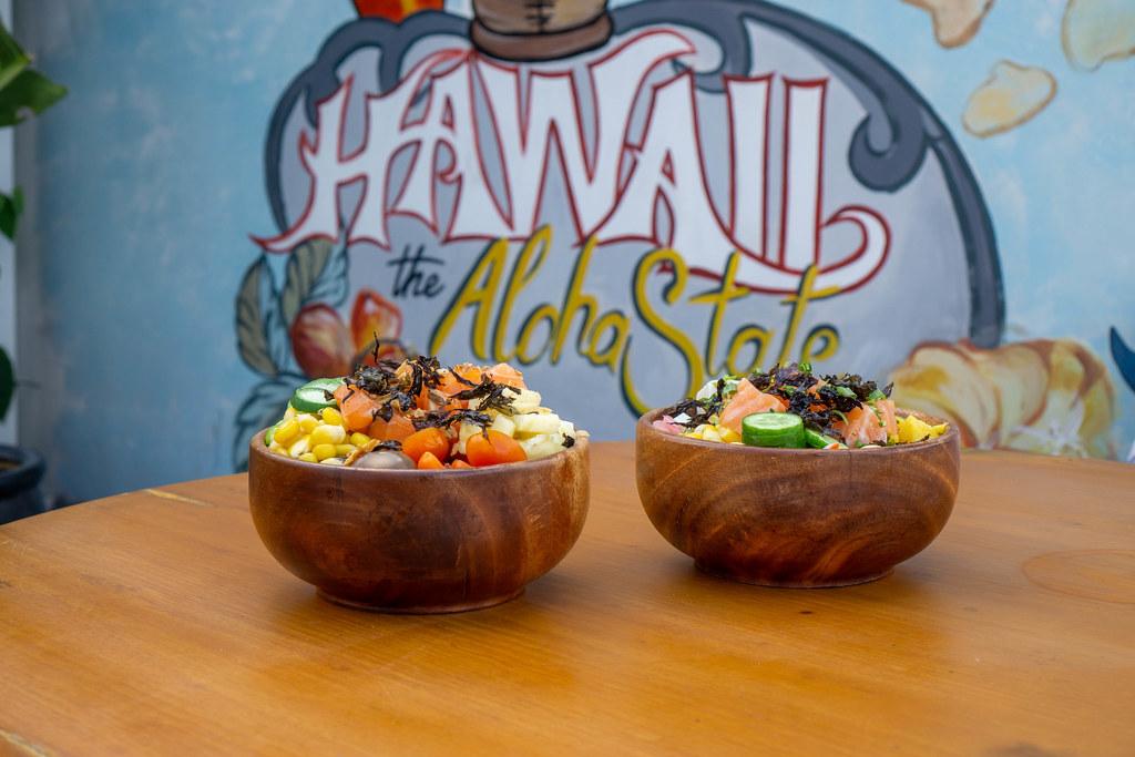 Zwei Gesunde Hawaiianische Poke Bowls auf einem Holztisch mit Hawaii the Aloha State Kunst im Hintergrund