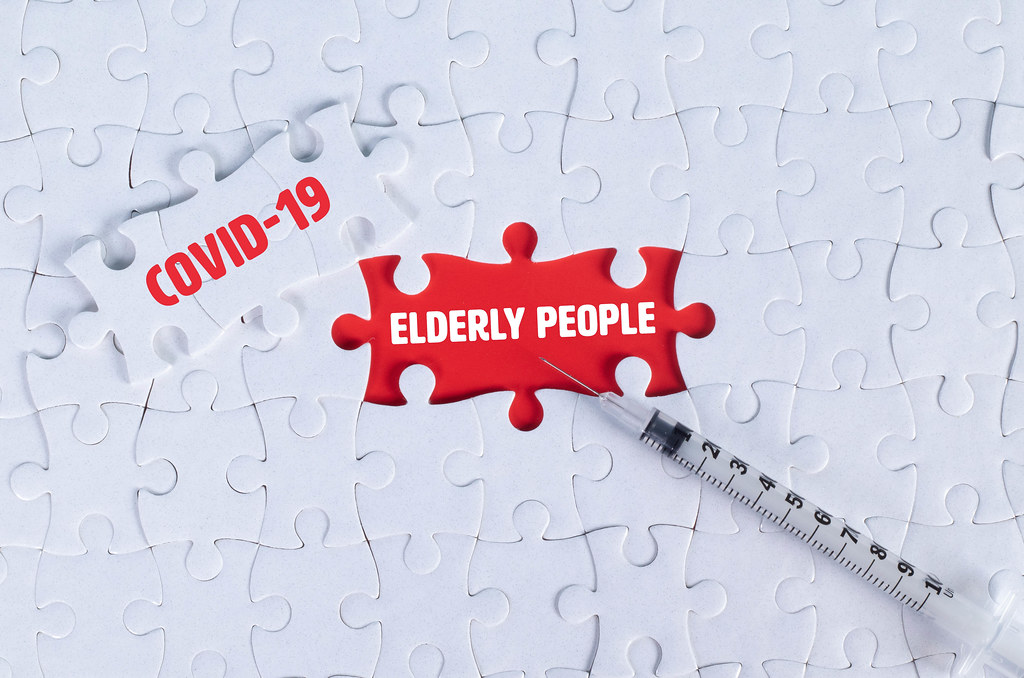 Syringe and missing puzzle pieces with text Covid-19 and Elderly people