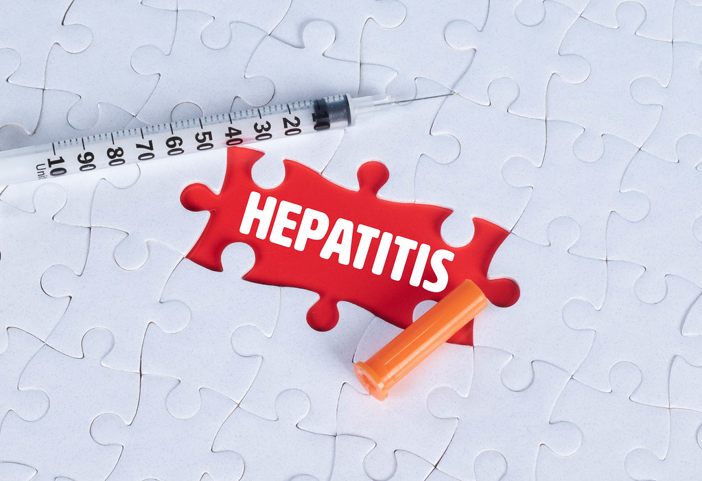 Syringe and missing puzzle pieces with a Hepatitis text