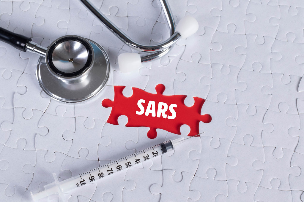 Stethoscope, syringe and missing puzzle with a SARS text