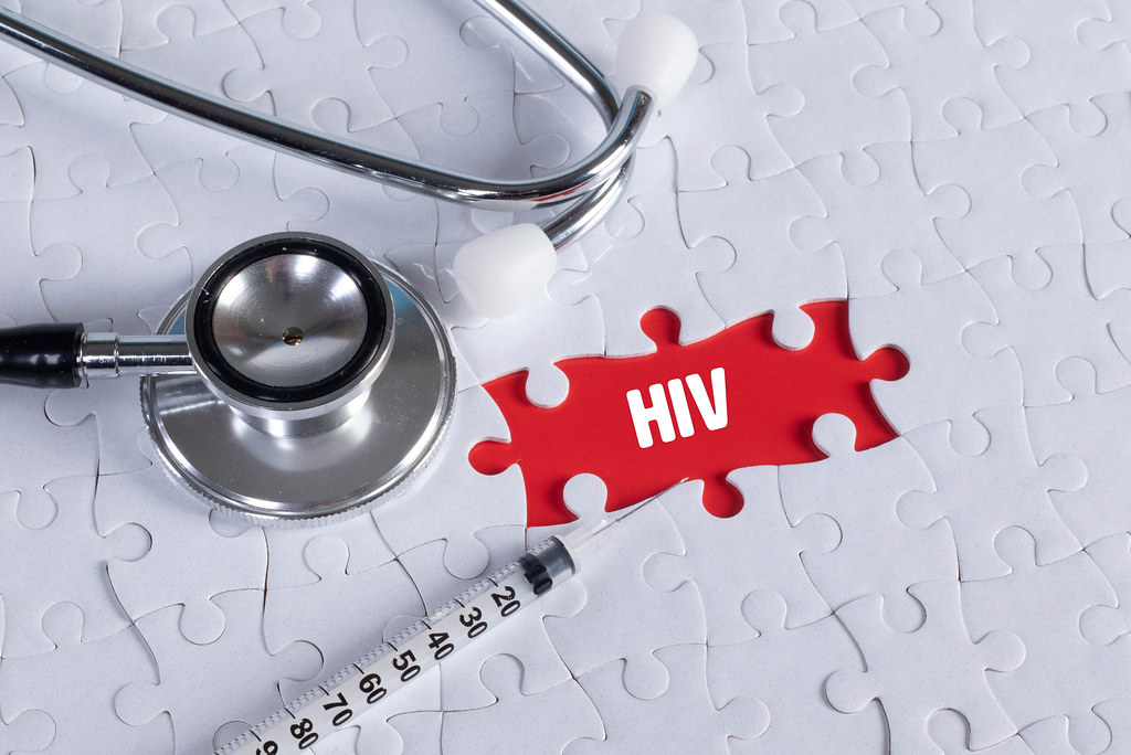 Stethoscope, syringe and missing puzzle with a HIV text