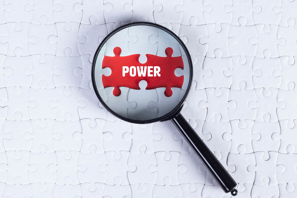 Magnifying glass over missing puzzle with a text Power