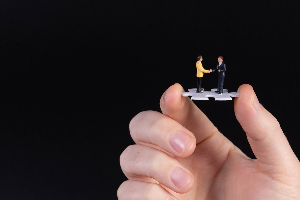 Hand holding puzzle piece with two businessman shaking hands