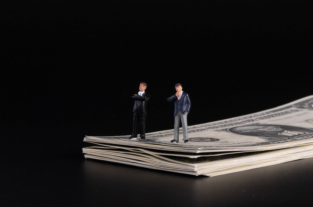 Two businessman standing on a stack of 100 Dollar banknotes