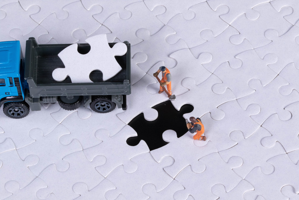 Truck with missing puzzle piece and two miniature workers