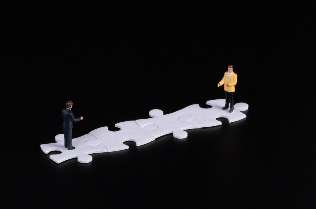 Two businessman standing on white puzzle pieces with black background
