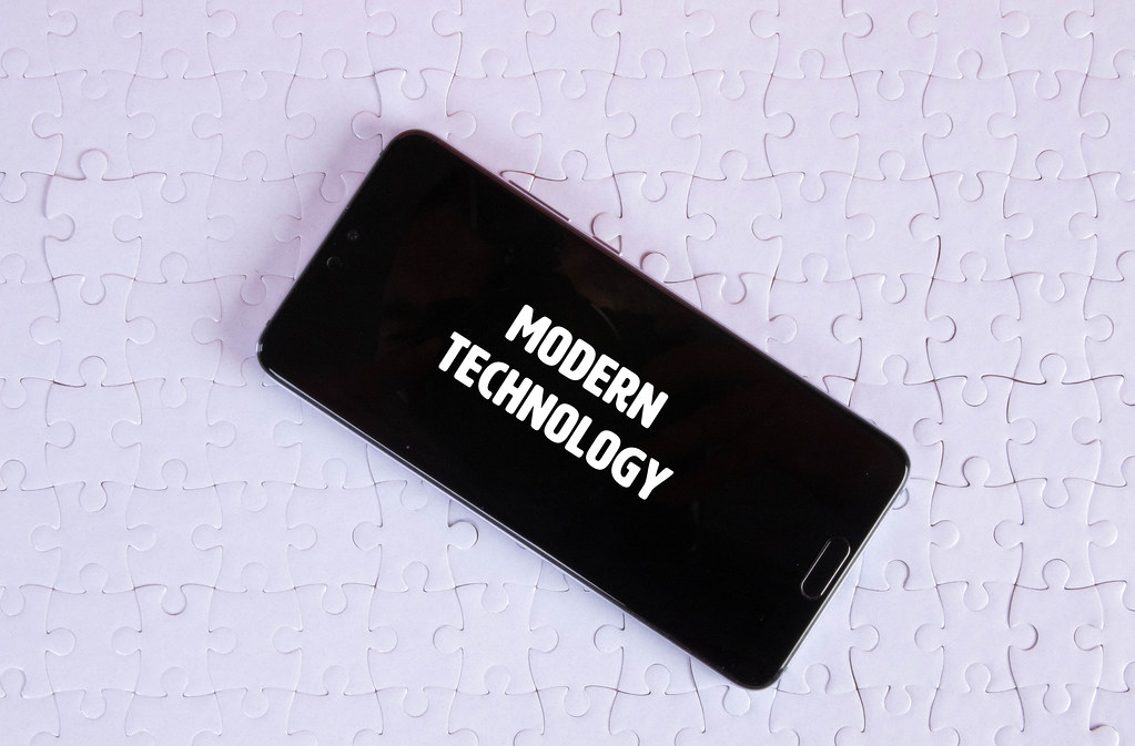 Smartphone on a white jigsaw puzzle with Modern Technology text