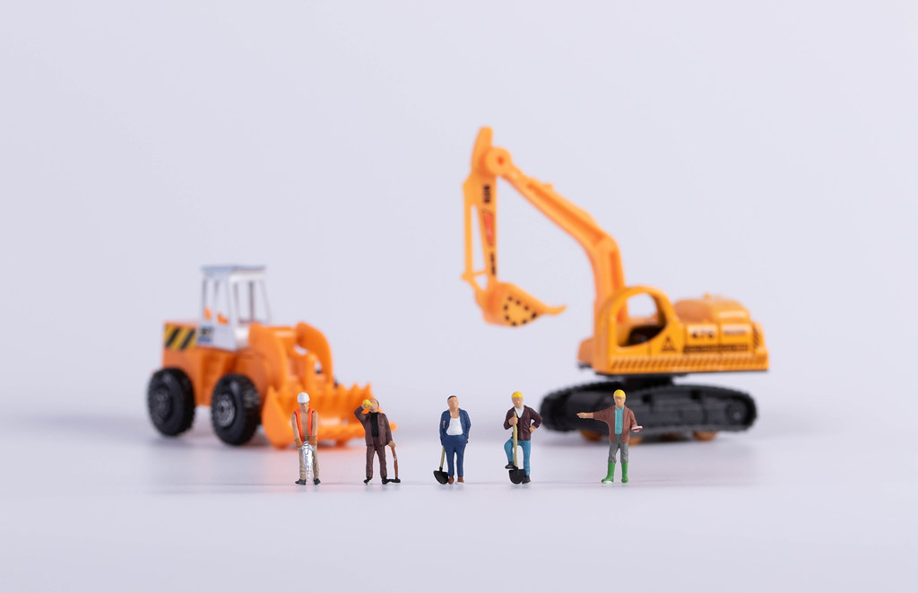 Construction workers with crawler excavator and excavator on white background