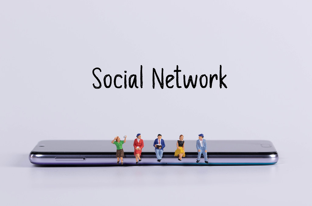Miniature people sitting on smartphone with Social Network text