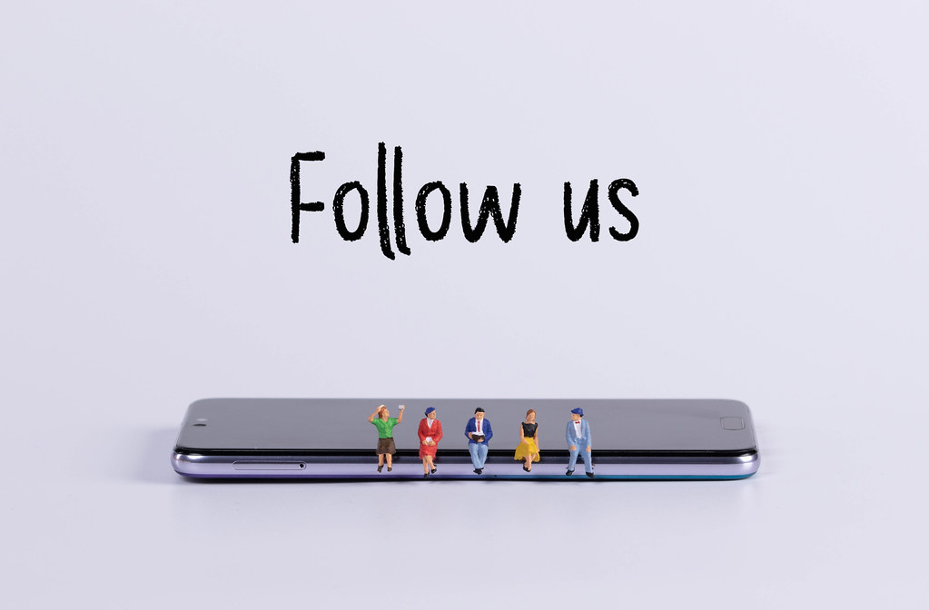 Miniature people sitting on smartphone with Follow us text