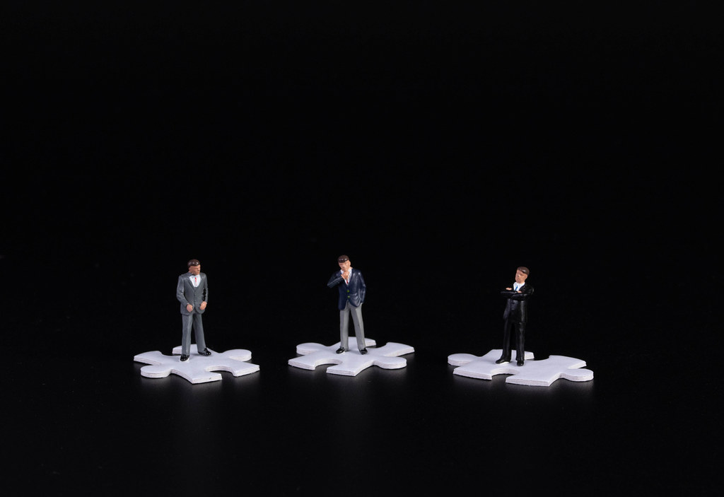 Group of businessman standing on puzzle piece wtih black background