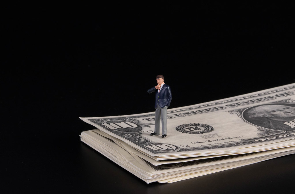 Businessman standing on a stack of 100 Dollar banknotes