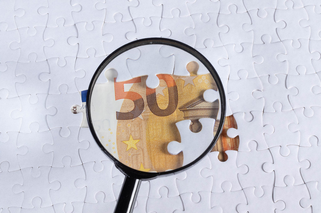 Magnifying glass over missing puzzle 50 Euro banknote