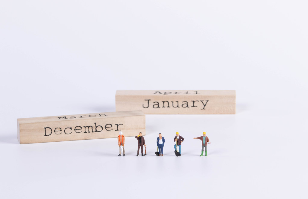 Group of workers with wooden block with December and January text