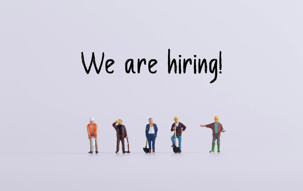 Group of workers with We are hiring text