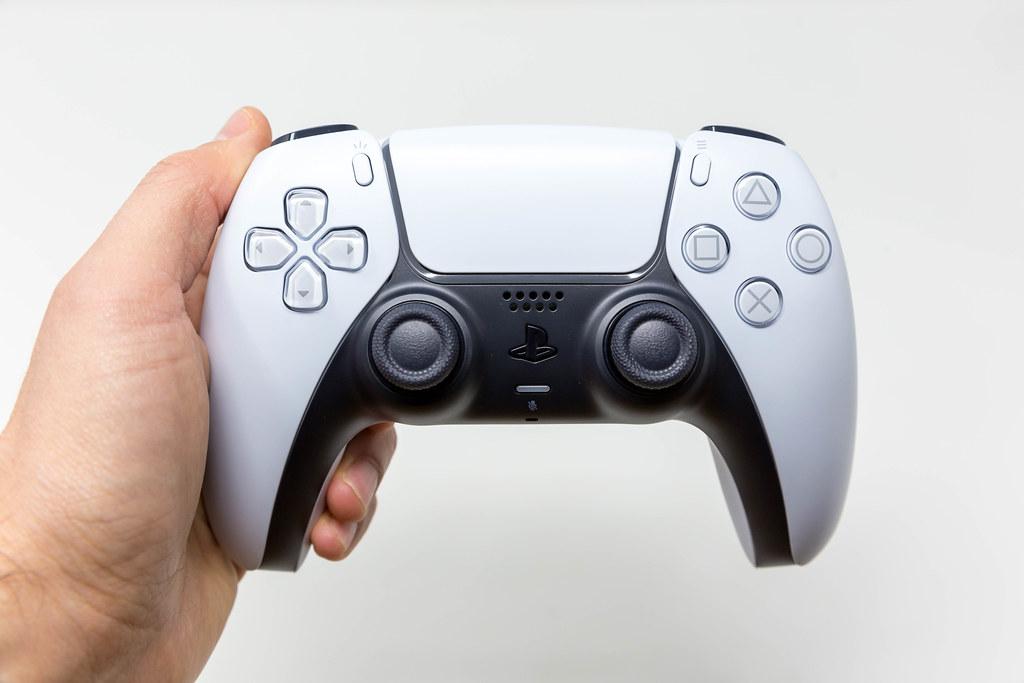 Person hält einen PlayStation 5 DualSense Wireless Controller in der Hand vor weißem Hintergrund
