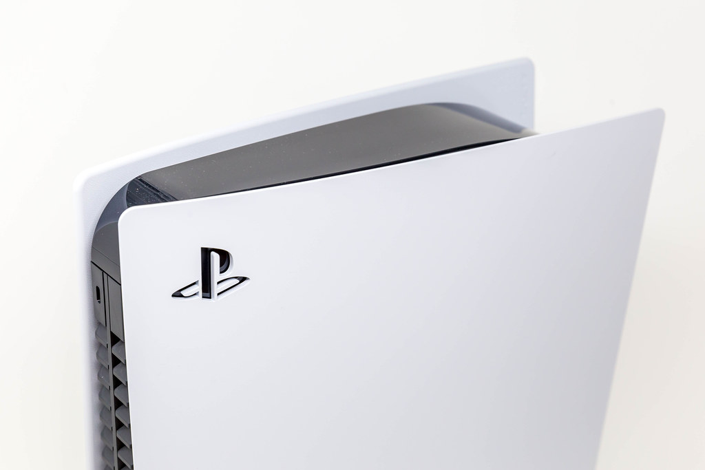 Close-Up Photo of Sony Logo on Upper Part of a Standing Sony PlayStation 5 on White Background