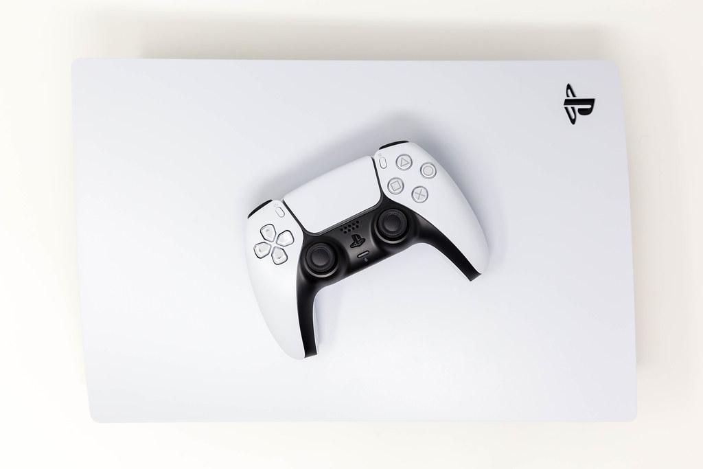 Sony DualSense Wireless-Controller auf einer liegenden Sony PlayStation 5 auf weißem Hintergrund Draufsicht