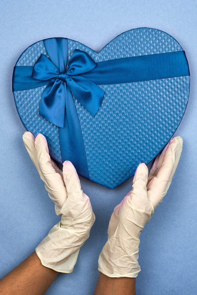 Female in medical gloves takes Valentine gift