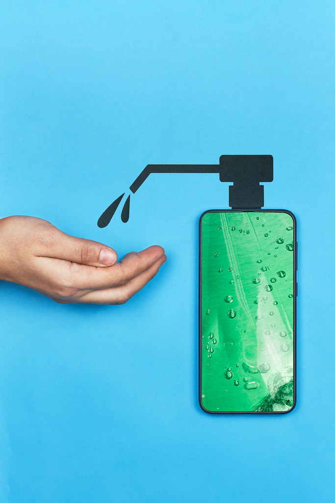 Woman disinfecting hand with mobile hand sanitizer