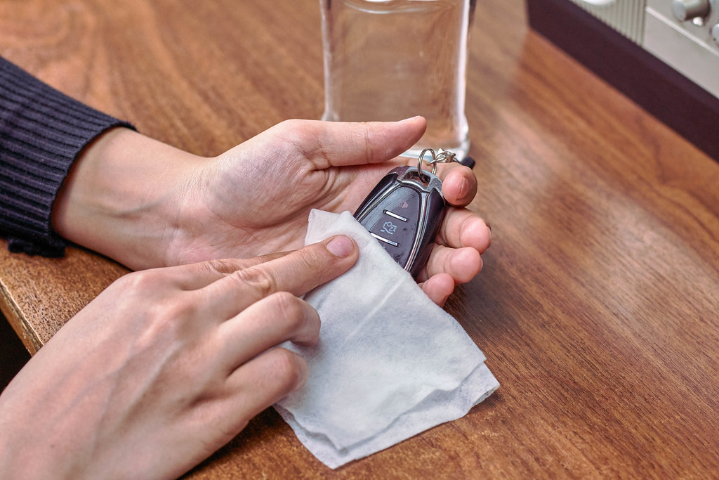 Woman disinfecting car remote controller with a wet wipe