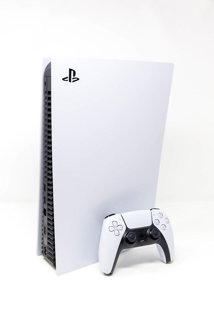 Eine stehende PlayStation 5 und der neue DualSense Wireless Controller vor weißem Hintergrund