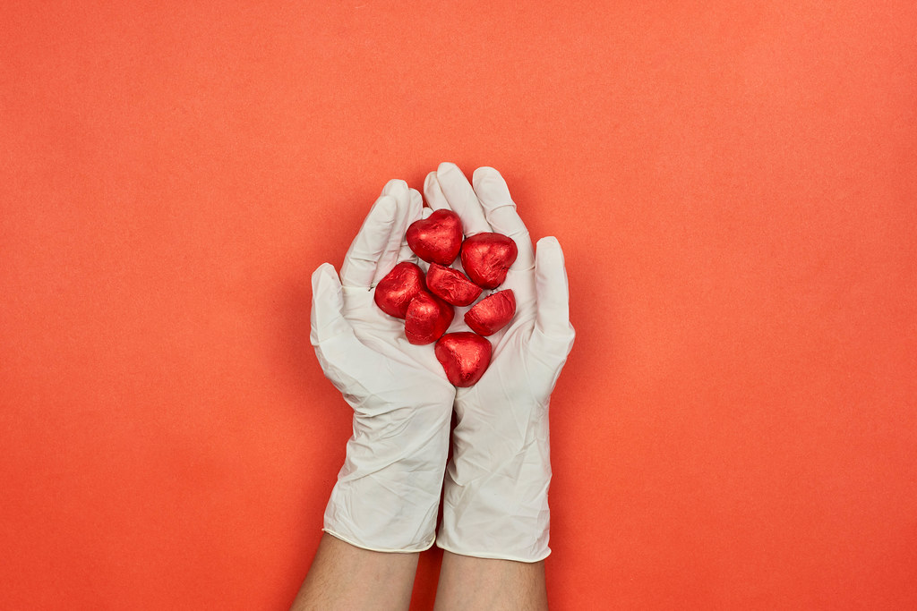 A female doctor in medical gloves holds in hands sweet chocolates