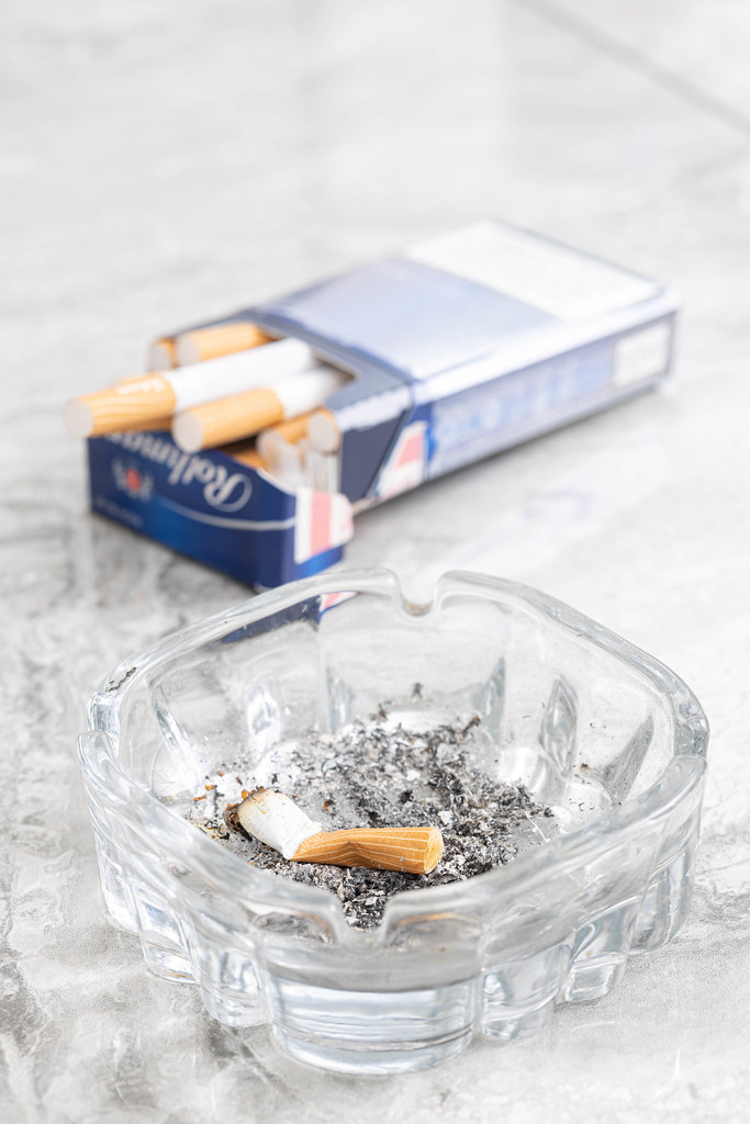 Smoked Cigarette in the Ashtray with cigarettes in the blurred background