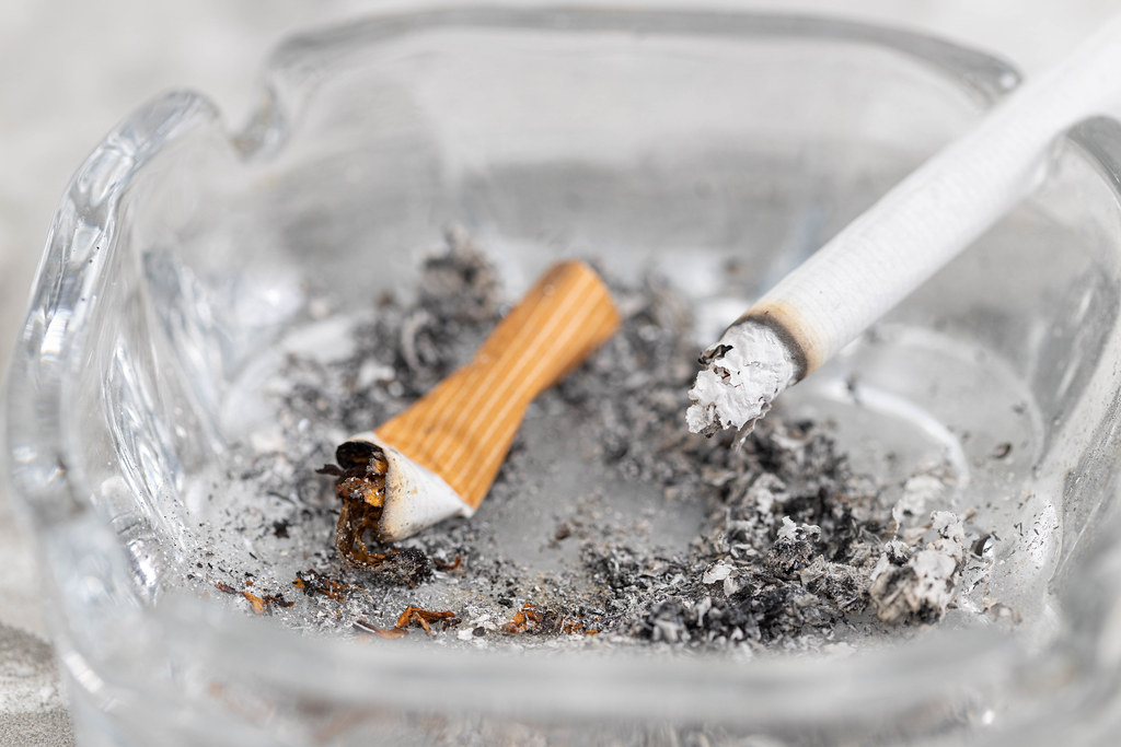 Dirty ashtray and smoked cigarettes with health danger concept