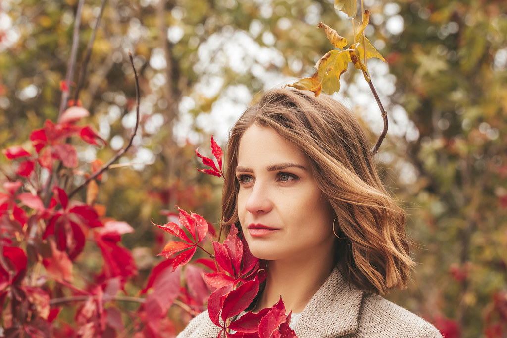 Beautiful girl with red leaves outdoors