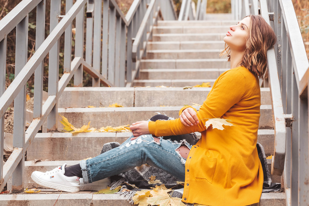 Beautiful young woman sitting on the steps with a yellow maple leaf in her hand