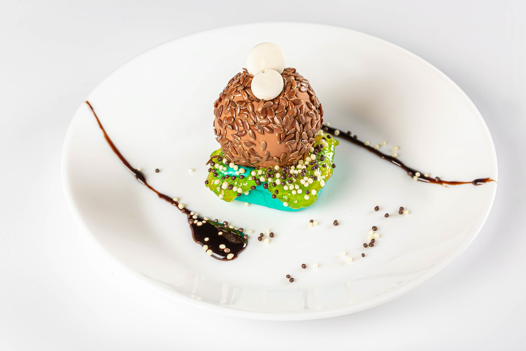 Sweet dessert with chocolate and flax seeds on a white plate