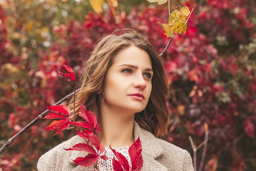Portrait of a girl on an autumn background with red leaves