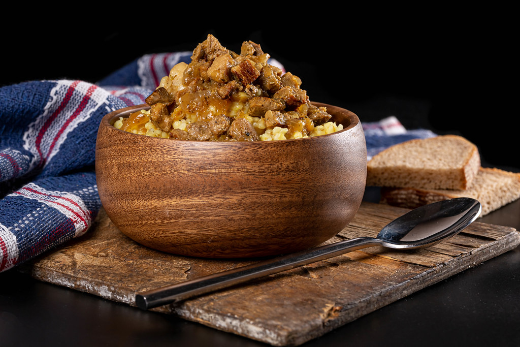 Wooden bowl with bulgur porridge and meat gravy