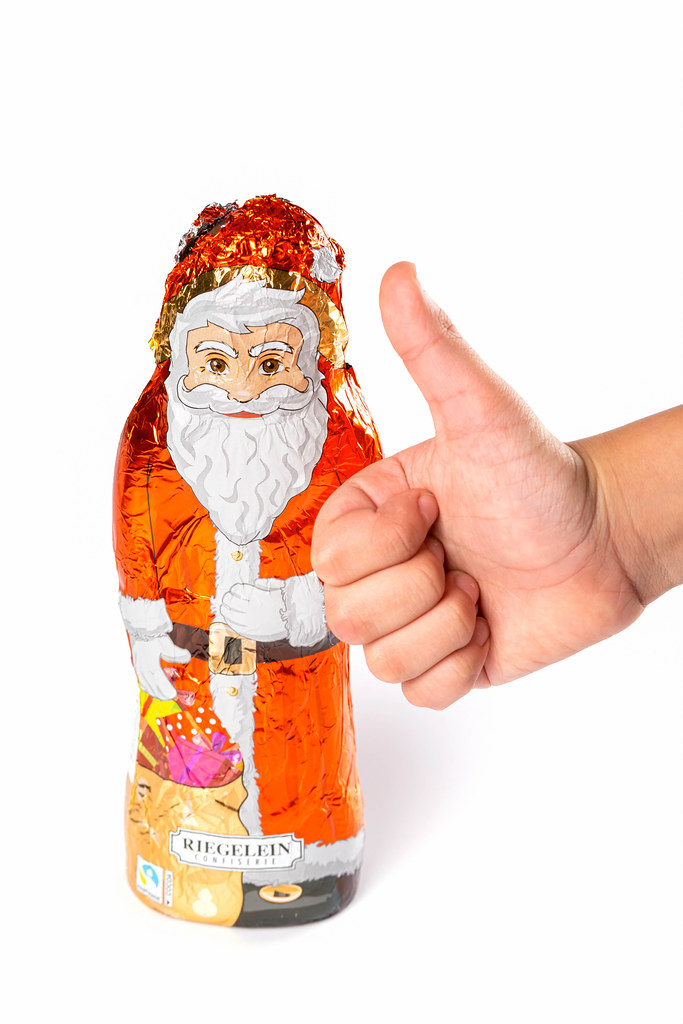 Figurine of chocolate santa claus and child's hand showing like