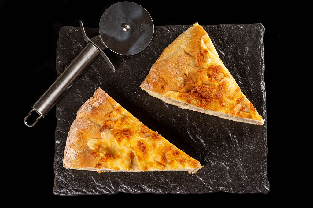 Top view, slices of khachapuri with meat and mozzarella on dark background
