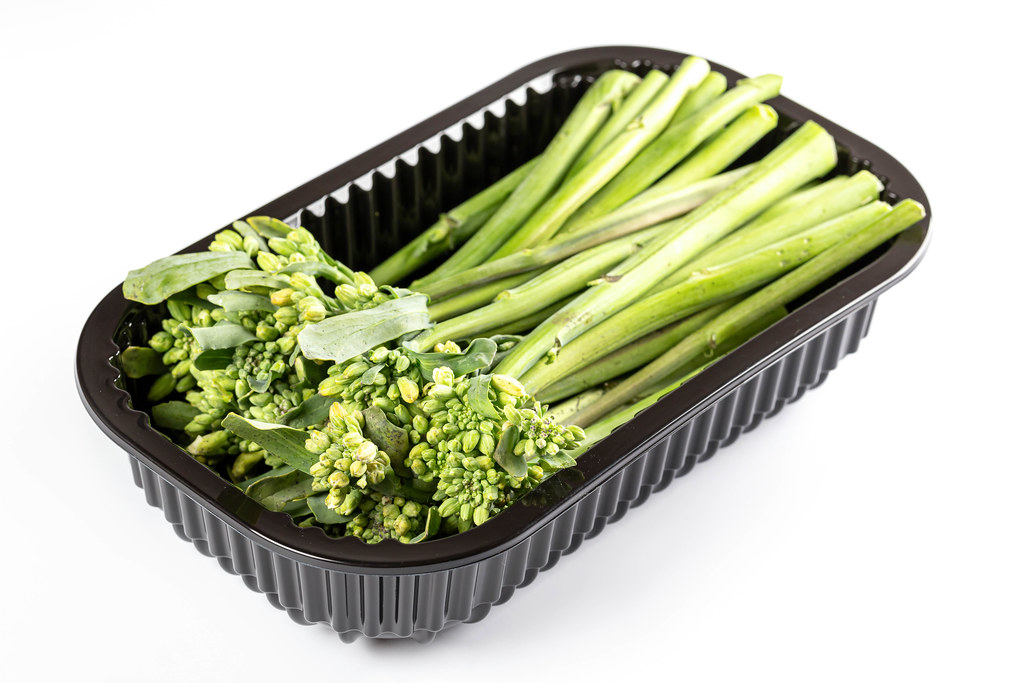 Green broccolini in a plastic container