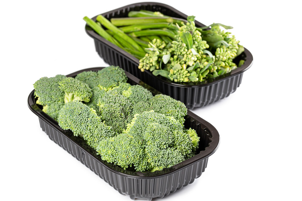 Containers with fresh broccoli and broccolini on white background