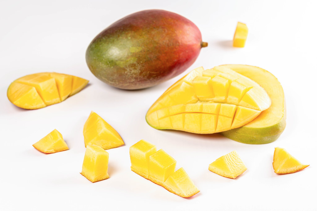 Fruit background with whole and chopped mango pieces