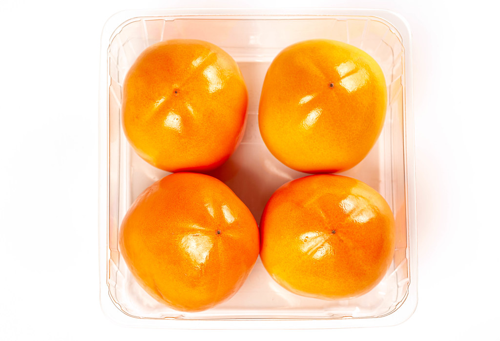 Top view persimmon fruits in plastic container