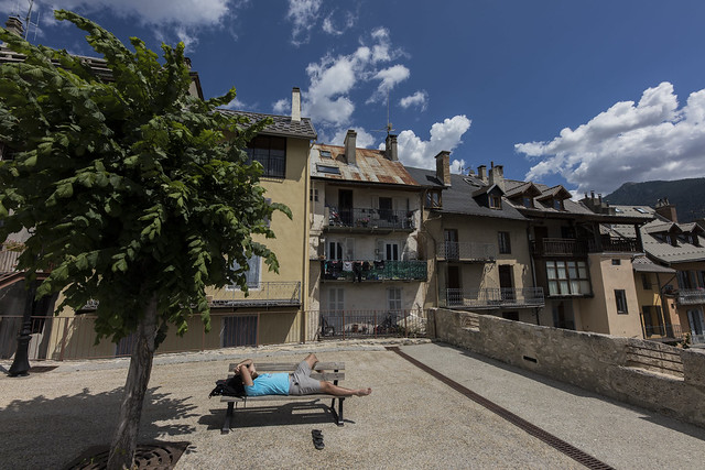 Square in Briançon and man sleeping