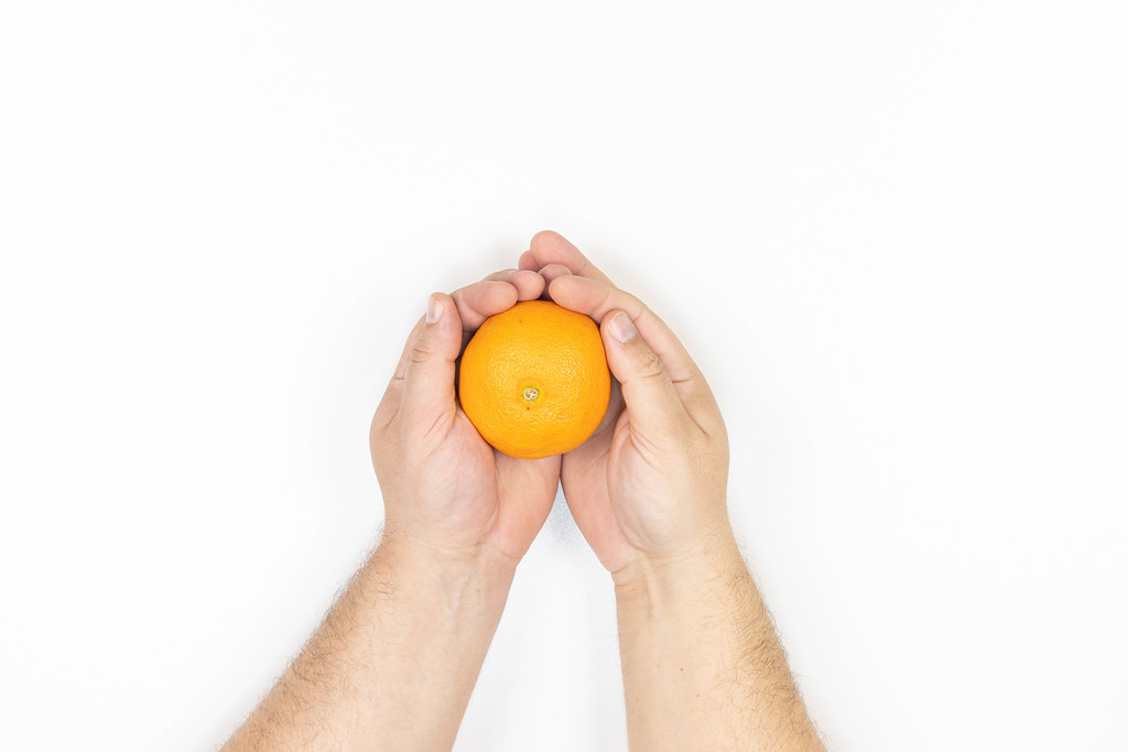 Orange in the hand isolated above white background with copy space