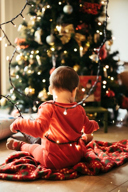 Young child sitting on the ground in a room decorated for christmas.