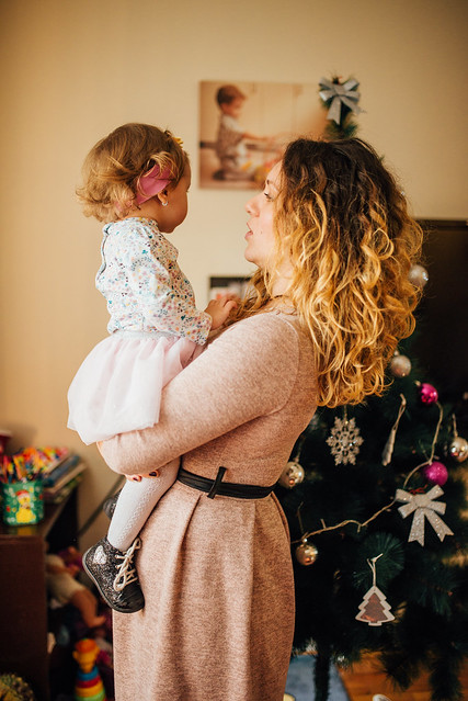 Mother holding her daughter in a room decorated for christmas.