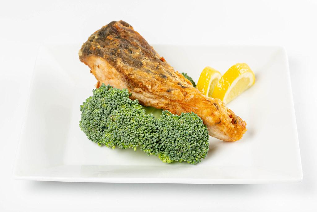 Fried fish with fresh broccoli and lemon