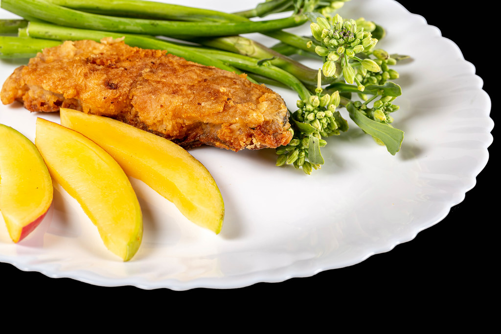 Fried fish with mango and broccolini, close-up
