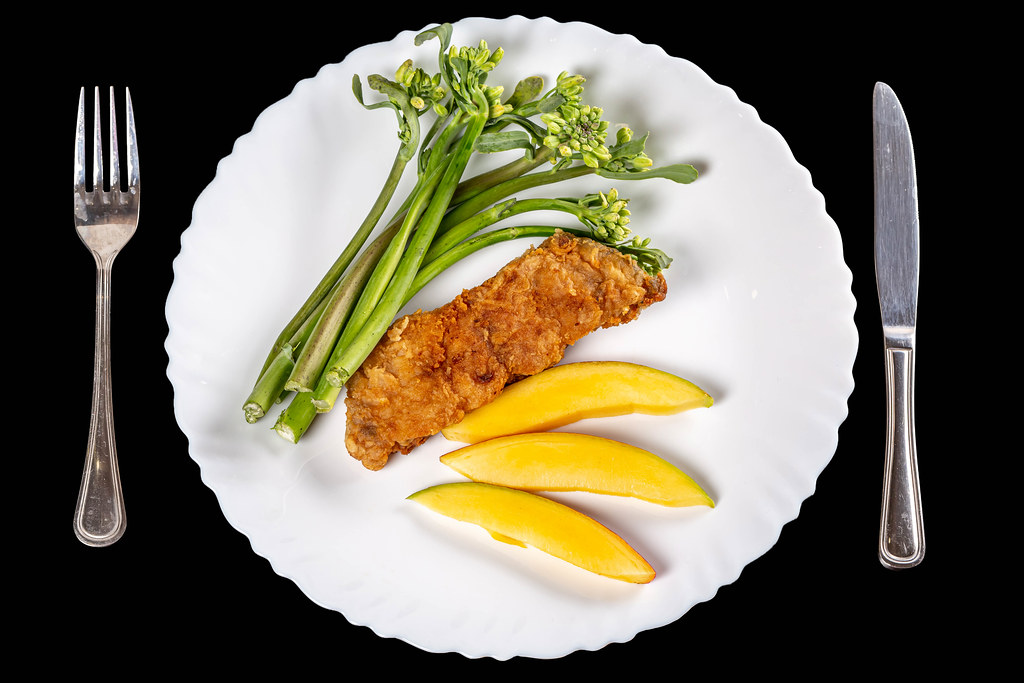 Top view, piece of fried white carp with mango and broccolini